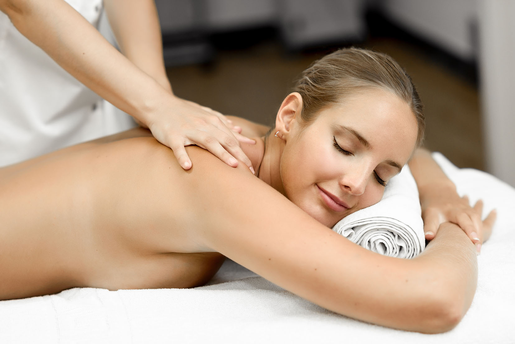Young blond woman having massage in the spa salon Massage and body care Body massage treatment. Smiling female.